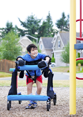 Disabled boy in walker walking up to a handicap inaccessible playground