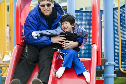 Father going down slide with disabled son